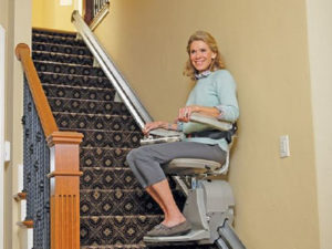 woman riding stairlift up stairs